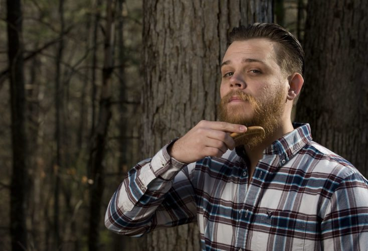 Brody Williams, owner/founder of  Backwoods Beard Company LLC, grooms his beard with one of his engraved combs. Williams, of Mount Jackson, has created a line of products to assist in growing and grooming the perfect beard.   Rich Cooley/Daily